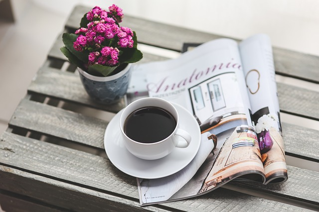 image of a cup of coffee, a magazine and a potted plant